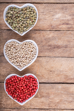 pounder: pepper in  cup in the shape of heart on wooden background