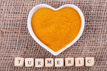 turmeric: Turmeric in  cup in the shape of heart on sack  cloth Stock Photo