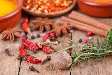 Various spices and herbs on wooden background photo