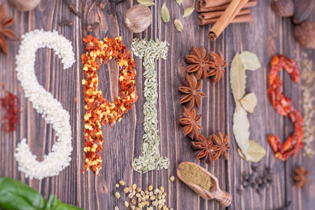 indian mustard: The word spice written with Different  spices  on a wooden background Stock Photo