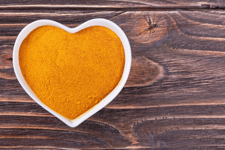 turmeric spice in a bowl in the form of heart on a wooden background