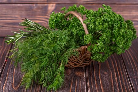 dill and parsley: dill, parsley, rosemary in the basket on wooden backgroun