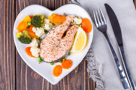 meat alternatives: Steamed salmon with vegetables on  plate in the form of heart on wooden background Stock Photo