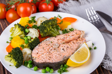 Steamed salmon with vegetables on  plate on wooden background Stock Photo