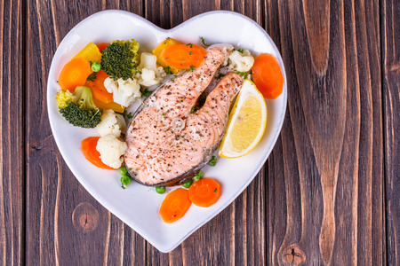 Steamed salmon with vegetables on  plate in the form of heart on wooden background Stock Photo