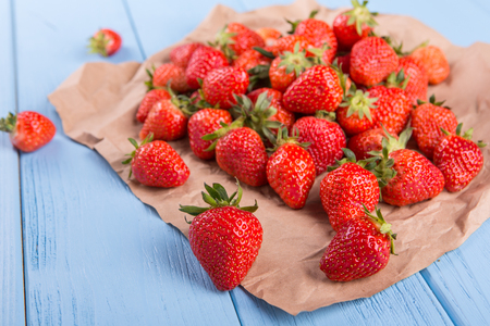 fresh strawberries on paper on wooden backgroun Stock Photo