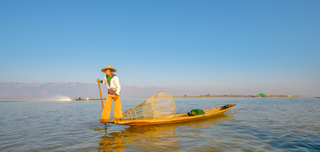 Burmese fisherman catching fish in traditional way. Inle lake, Myanmar (Burma)