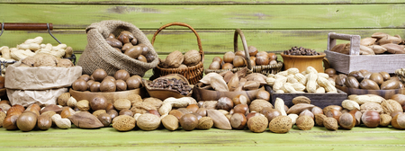 panorama of various nuts on a wooden background