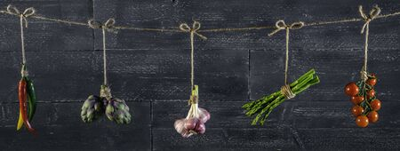 panorama of fresh vegetables and spices on wooden background