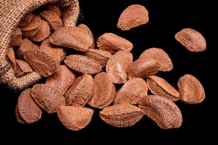 Paranuts in bag, vegetarian food in wooden bowls, on black background
