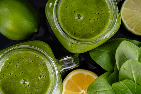 Healthy green smoothie with spinach, mango, orange, lime, apple, citrone in glass jars top view Reklamní fotografie