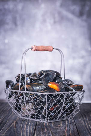 Fresh Mussels in a Basket on a wooden board. Seafood. Dark background