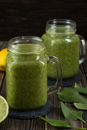 Healthy green smoothie with spinach, mango, orange, lime, apple, citrone in glass jars. Stockfoto