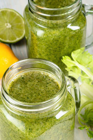 Healthy green smoothie with spinach, mango, orange, lime, apple, citrone in glass jars.
