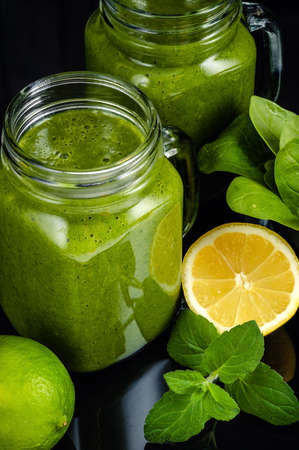 Healthy green smoothie with spinach, mango, orange, lime, apple, citrone in glass jars. Reklamní fotografie