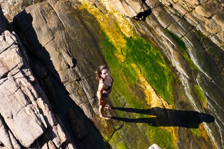 Girl on top of slippery rocks in Buzios, Rio de Janeiro, Brazil