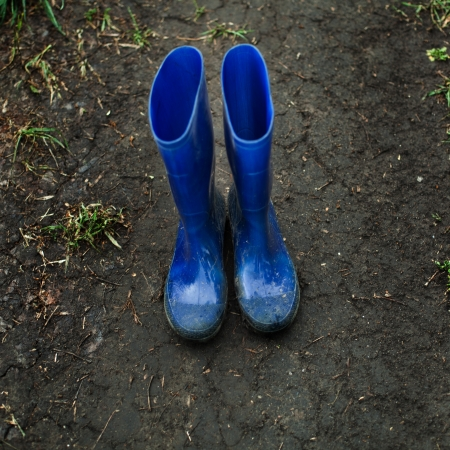 gumboots: blue gumboots on the dirty village road