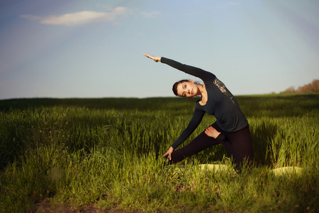 ideally: beautiful young brunette woman doing yoga in a field of wheat under sunrays