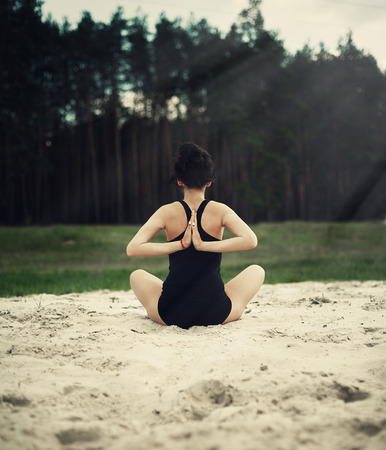 ideally: beautiful girl is engaged in yoga in the forest on the sand Stock Photo