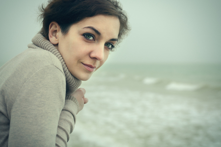 thoughtful woman: portrait of a beautiful woman at the sea
