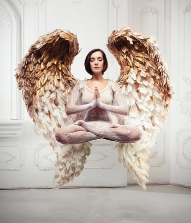 Levitación de yoga de mujer joven y concepto de meditación. Objetos que vuelan en la habitación. Foto de archivo