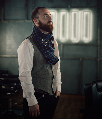 successfull: Handsome bearded man hipster with stylish beard in white shirt and chekered scarf standing with serious face in beauty salon or barbershop Stock Photo