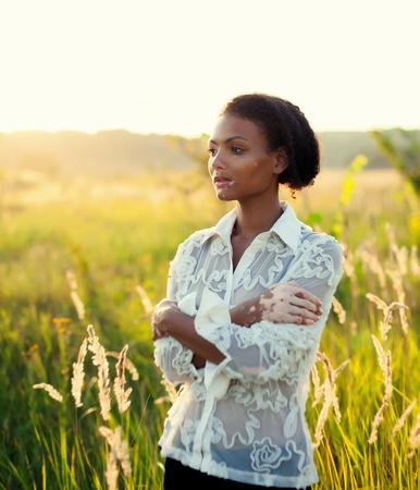 夕陽が美しいフィールドに白斑病の若いブルネット美女 写真素材