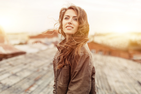 Young curly attractive woman with good mood enjoying beautiful city landscape while standing on a roof of building, charming smiling hipster girl relaxing after excursion during her amazing spring weekend. Dressed in a brown leather jacket.