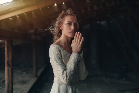 Beautiful girl in in white vintage dress with curly hair posing on the attic. Woman in retro dress. Worried sensual emotion . Retro fashion. Dramatic mood.