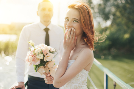 redhead bride in white dress holding flower bouqet and groom in white shirt and tie are standing on the bridge in the wedding summer day. Woman is pleasantly surprised by the gift Stock Photo