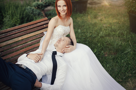 Bridegroom lies on the beautiful girl in a wedding dress in the public park on the bench. Bride is redhead put hand on the msn and smiling Stock Photo