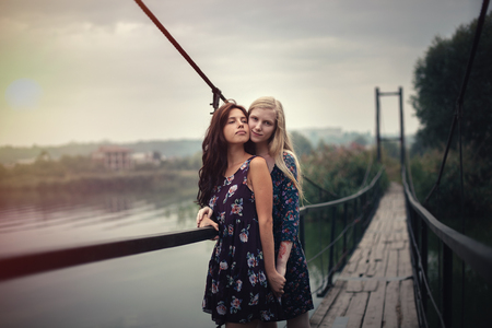 two beautiful young girlfriends blonde and brunette embracing on lake bridge on evening sunst. Rural scene. Women lesbians, hugging each other Stock Photo