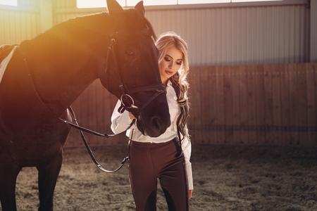 Belle jeune fille blonde élégante debout près de son uniforme de dressage de cheval noir uniforme blouse blanche et pantalon brun. Portraite intérieur dans la salle d'équitation. Banque d'images - 84323991