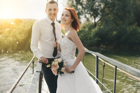 redhead bride in white dress holding flower bouqet and groom in white shirt and tie are standing on the bridge in the wedding summer day