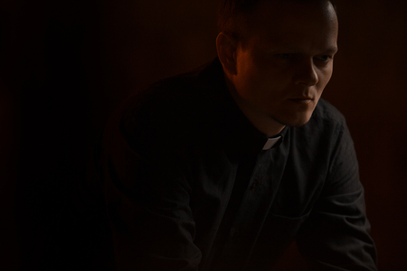 Portrait of handsome catholic priest or pastor with dog collar, dark red background. folded his hands in prayer