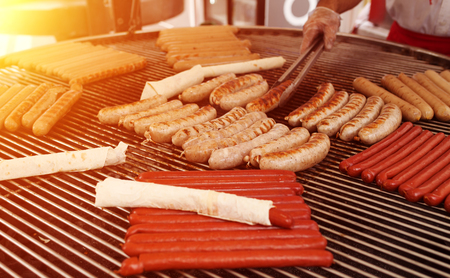 Fresh sausage and hot dogs grilling outdoors on a gas barbecue grill. Street food Stock Photo