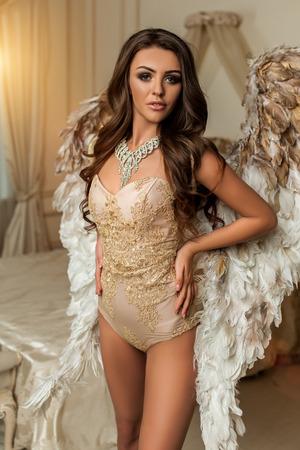 Angel muse in th witte interieur krullend mooie vrouw met grote witgouden vleugels