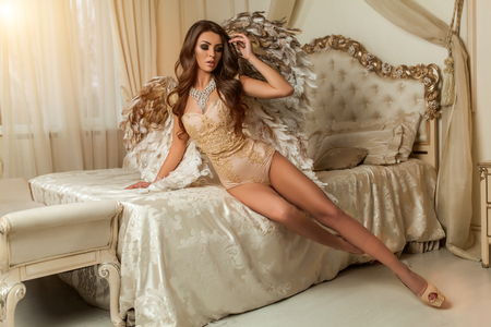 beautiful curly brunettу woman with big gold and white wings in the house lies on the bed Archivio Fotografico