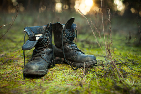 Old leather combat boots on green grass with free copy space on the left side.
