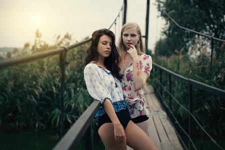 Deux belles jeunes copines blonde et brune embrassant sur le pont du lac le soir sunst. Scène rurale. Femmes lesbiennes, se serrant les unes les autres Banque d'images - 94057134