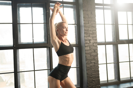 beautiful athletic blonde dancer and athlete in a black top and shorts with a beautiful muscular body doing stretching exercises near a large window