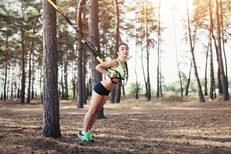 Beautiful young woman doing trx exercise with suspension trainer sling in the outdoors pine forest healthy