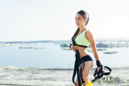 Young attractive woman rest after suspension trx training with fitness straps outdoors in the nature Imagens