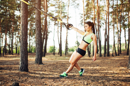 Beautiful young woman doing trx exercise with suspension trainer sling in the outdoors pine forest healthy Standard-Bild - 97581600
