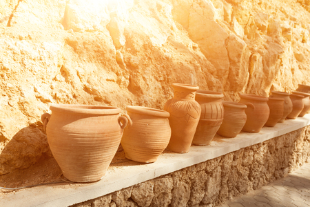 many large clay pots standing in a row outdoor