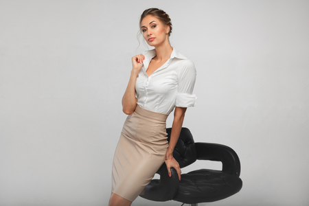 beautiful business woman in a white office shirt leaning on a bar stool of black leather. The concept of office etiquette. And gender equality Archivio Fotografico