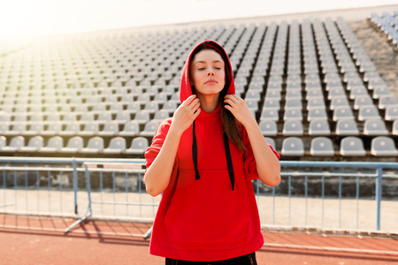 Beautiful lady runner in warm clothes on the stadium looking aside. Wearing red hood. Casual sport wear concept