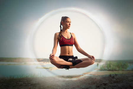 beautiful young girl sportswoman in sportswear levitates in lotus position on nature near lake Yoga tranquility meditation concept