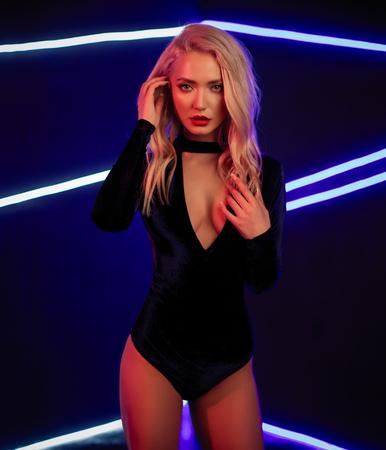 Fashion art photo of elegant model in seductive black swimsuit with light neon colored club spotlights Night club concept