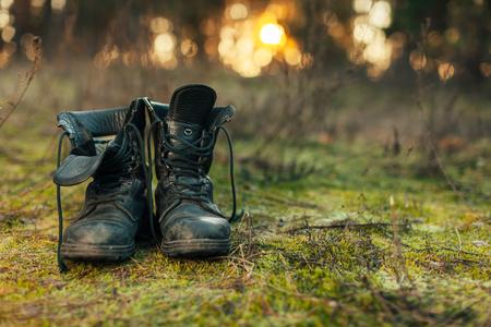 Close up of vintage pair of walking boots on boulder grassland background. Hard travel concept